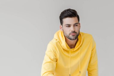 Handsome young man in yellow hoodie looking away isolated on white stock vector
