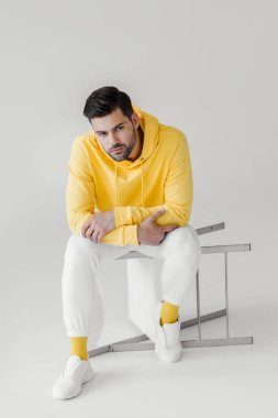 handsome young man in yellow hoodie sitting on flipped chair on white