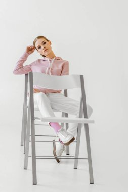 serious fashionable young woman sitting on chair and looking at camera on white
