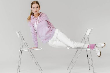 attractive young woman lying on two chairs on white