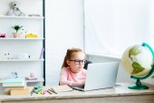 beautiful child in eyeglasses using laptop while studying at desk at home