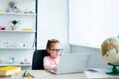 gyönyörű vörös hajú iskolás használ a laptop otthon tanulmányai