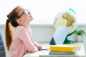 Fotografie side view of smiling red haired schoolgirl in eyeglasses using laptop at desk