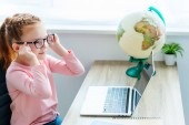 Fotografie cute smiling child using laptop while sitting at desk