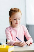 Photo beautiful smiling schoolgirl sitting at desk and taking notes