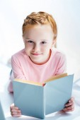 adorable child holding book and smiling at camera