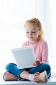 Fotografie krásné usměvavé dítě pomocí digitálních tabletu, zatímco sedí na okenním parapetu