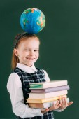 Fotografie adorable little schoolchild with globe on head holding pile of books and smiling at camera
