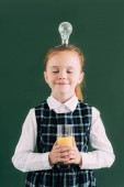 Fotografie happy little schoolgirl with closed eyes and light bulb on head holding glass of orange juice