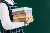 Fotografia cropped shot of schoolgirl holding pile of books while standing near blackboard