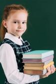 Fotografie roztomilá malá školačka drží hromadu knih a usmívá se na kameru