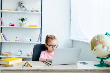 cute little schoolchild in eyeglasses using laptop while studying at home