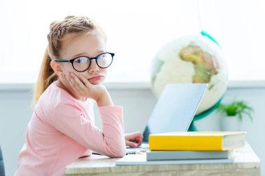 bored child in eyeglasses looking at camera while studying with laptop and books