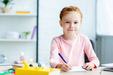 beautiful redhead schoolgirl smiling at camera while writing in notebook at desk