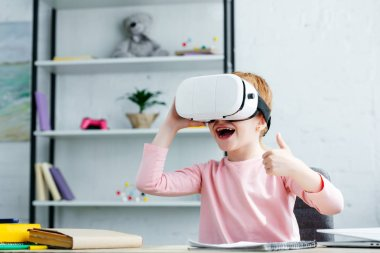 adorable happy schoolchild using virtual reality headset and showing thumb up