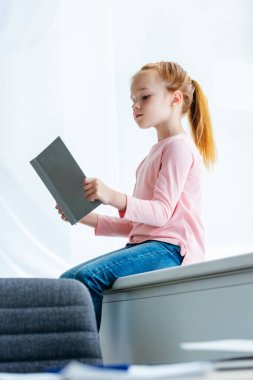 low angle view of cute little schoolgirl sitting on windowsill and reading book