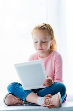 beautiful smiling child using digital tablet while sitting on windowsill