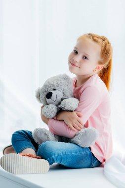beautiful happy redhead kid hugging teddy bear and smiling at camera
