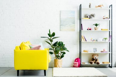 cozy interior with yellow couch and books with toys on shelves