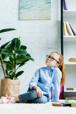 Beautiful little redhead child in eyeglasses sitting on carpet and looking up while studying at home stock vector