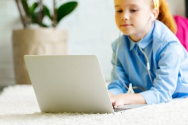 Cropped shot of cute little child in earphones lying on carpet and using laptop stock vector