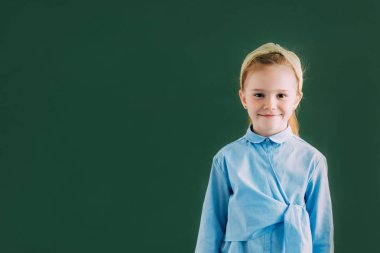 Adorable little redhead schoolgirl standing near blackboard and smiling at camera stock vector