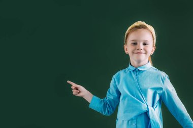 beautiful red haired schoolgirl pointing at blank chalkboard and smiling at camera