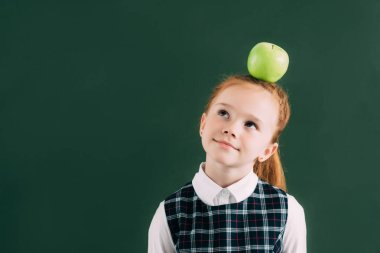 pensive little red haired schoolgirl with apple on head looking away