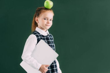 beautiful little schoolgirl with apple on head holding laptop and looking at camera