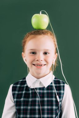 Happy little schoolgirl with apple on head and earphones smiling and looking at camera stock vector