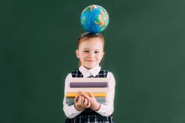 Little redhead schoolgirl with globe on head holding pile of books and smiling at camera stock vector