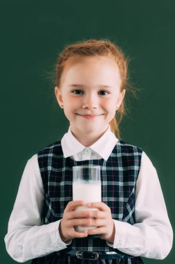 adorable little schoolgirl holding glass of milk and smiling at camera