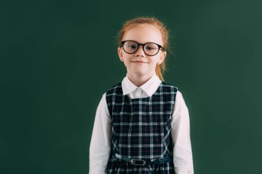 adorable little schoolgirl in eyeglasses standing near chalkboard and smiling at camera