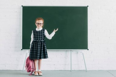 adorable little schoolgirl with backpack showing blank blackboard and smiling at camera
