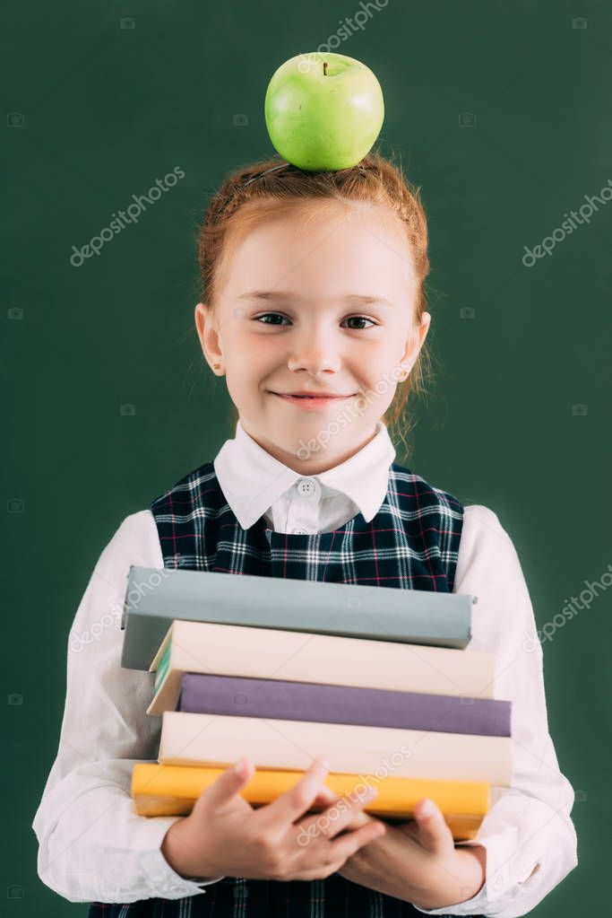 Adorable little redhead schoolgirl with apple on head holding pile of books and smiling at camera stock vector