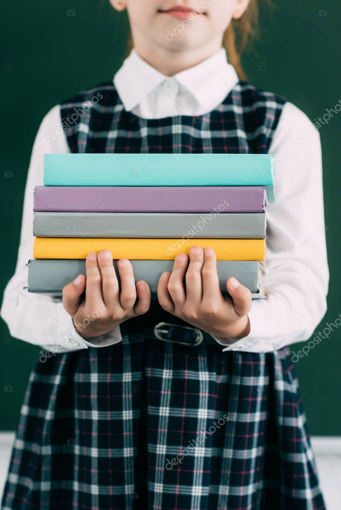 Cropped shot of cute little schoolgirl holding pile of books stock vector