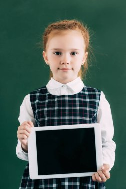 Beautiful little schoolgirl holding digital tablet with blank screen and looking at camera stock vector