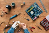 cropped image of man with robotic hand holding wires with tools at wooden table