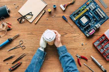 cropped image of electronic engineer with prosthetic arm holding paper cup on table with tools