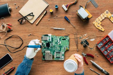 cropped image of electronic engineer with prosthetic arm soldering motherboard and holding paper cup