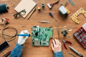 Fotografie cropped image of electronic engineer with robotic hand fixing motherboard by soldering iron at table surrounded by tools