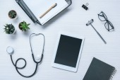 Fotografie elevated view of doctor workplace with textbook, stethoscope, reflex hammer and digital tablet on table
