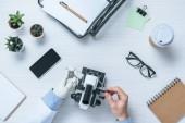 Oříznout záběr mužské vědce s protézu pomocí mikroskopu u stolu