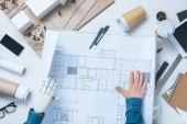 částečný pohled mužského architekta s protetickou rukou při pohledu na plán
