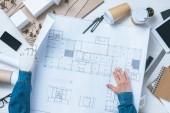 Teilansicht des männlichen Architekten mit prothetischem Arm, der mit Bauplan am Tisch mit Lineal, Smartphone und digitalem Tablet arbeitet