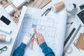 cropped image of male architect with prosthetic arm drawing on blueprint at table