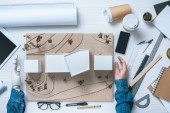 cropped image of male architect with prosthetic arm making model of house at table with coffee cups, rulers and blueprint