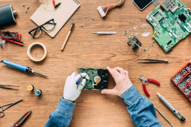 cropped image of man with prosthetic arm fixing hard disk by screwdriver on wooden table
