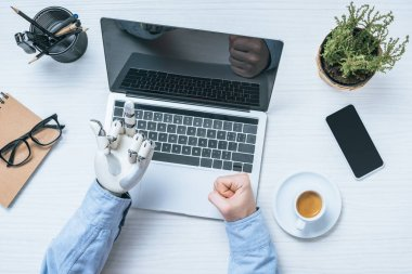 cropped image of businessman with prosthetic arm showing middle finger to laptop screen at table in office