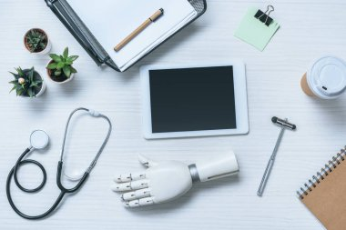 top view of doctor workplace with prosthetic arm, stethoscope, reflex hammer and digital tablet with blank screen on table